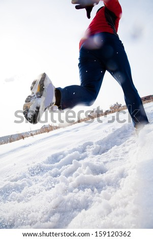 Athletic man running in winter day unrecognizable