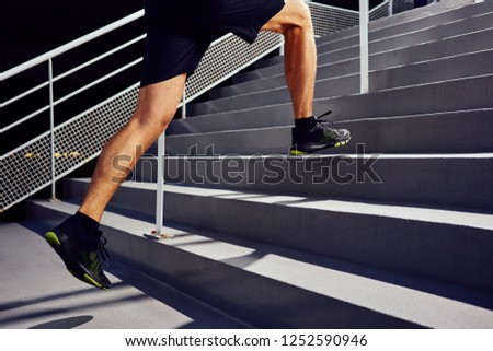 Athletic man running up staircase. Jogger working out