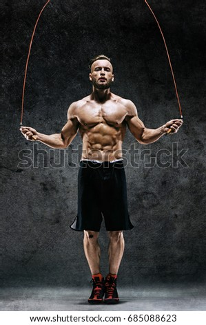 Athletic man skipping with a jump rope on dark background. Best cardio workout  #685088623