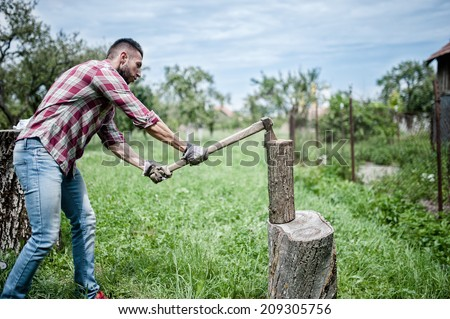 athletic man splitting wood and cutting firewood with axe