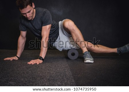 Athletic man using a foam roller to relieve sore muscles after a workout.  #1074735950