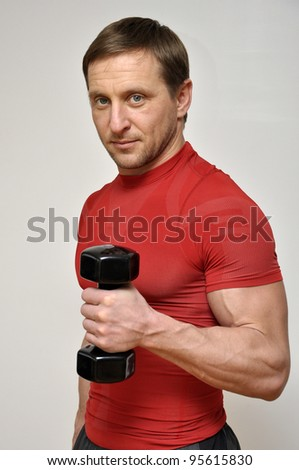 Athletic man  with a dumbbells over light background