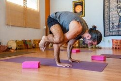 athletic man with beard practicing balance in yoga class on the floor