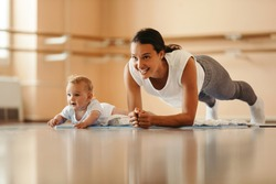 Athletic mother exercising in plank position while being with her baby on sports training. Copy space.