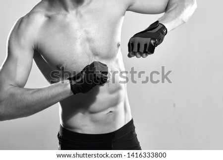 Athletic muscled man athlete in gloves power muscles bodybuilder