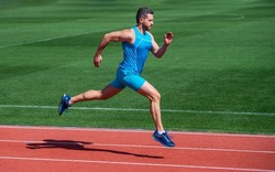 athletic muscular man running in sportswear on stadium track, stamina