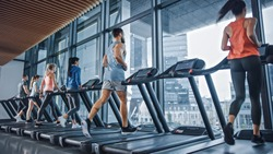 Athletic Muscular Man Running on a Treadmill, Leg and Cardio Day. Strong Man Training in the Modern Gym Fitness Club with Window Cityscape View. Back View Shot