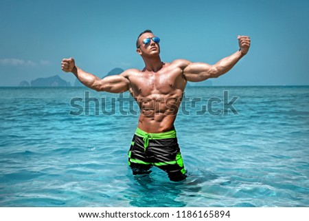 Athletic muscular young sexy wet naked guy posing in the ocean in board shorts