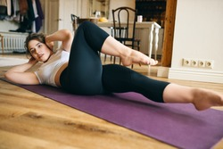 Athletic muscular young woman lying on back with hands behind head, alternate sides while doing bicycle crunches, bringing elbow toward knee, working out abs and core muscles. Fitness and sports