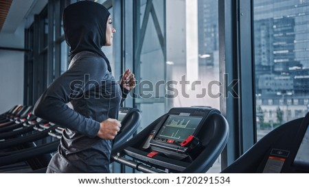 Athletic Muslim Sports Woman Wearing Hijab and Sportswear Running on a Treadmill. Energetic Fit Female Athlete Training in the Gym Alone. Urban Business District Window View. Side View Portrait