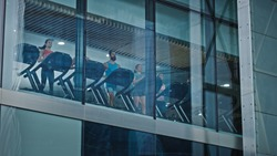 Athletic People Running on Treadmills, Doing Fitness Exercise. Fit and Muscular Athletes Actively Training in the Modern Gym. Sports People Workout. Low Angle Shot From Outside the Building