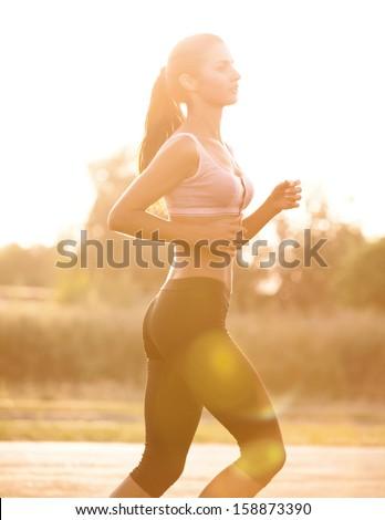 Athletic Runner Training in a park for Marathon. Fitness Girl Running outdoors