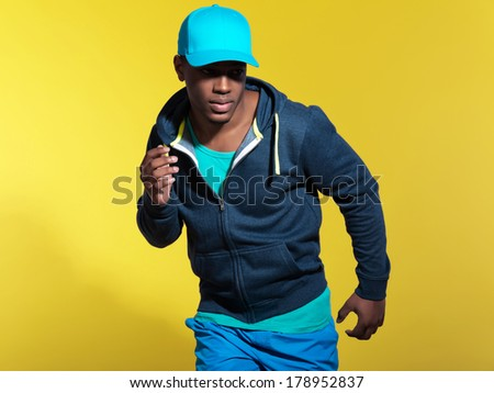 Athletic runner wearing blue sportswear fashion. Black man. Blue cap and sweater. Intense colors. Studio shot against yellow background.