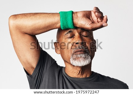 Athletic senior mean wiping off sweat from his forehead