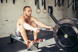Athletic shirtless male doing workouts on a back with power exercise machine in a gym club.