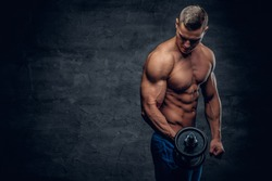 Athletic shirtless young male fitness model holds the dumbbell with light isolated on dark background.