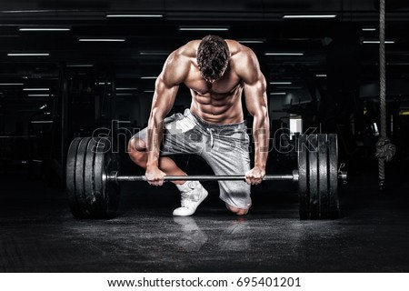 Athletic shirtless young sports man - fitness model with barbell in gym.
