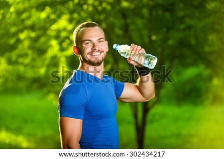Athletic sport man drinking water from a bottle. Cold drink after outdoor fitness.