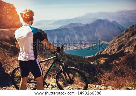 Athletic sportsman cyclist standing with bike enjoying beautiful view.