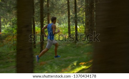 Athletic sportsman goes for a long relaxing jog along an empty forest trail on an idyllic summer day. Sporty Caucasian male exploring the tranquil wilderness by jogging through the coniferous forest. #1370434178