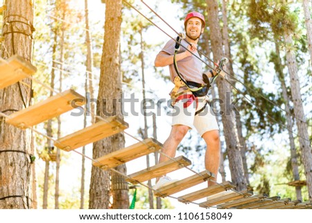 Athletic Sporty Guy Doing Activity in Adventure Park with all Climbing Equipment like Helmet, Rope and Carabiner. Active People Climb on the Trees and Having Fun Outdoors Enjoying Nature Landscape.  #1106158049
