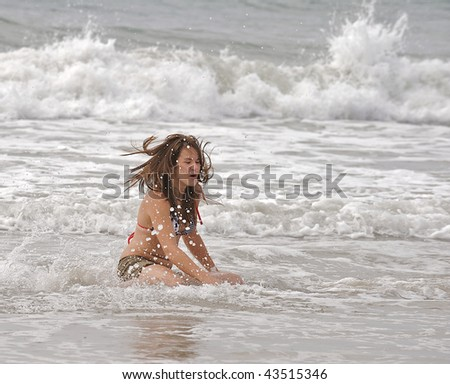 stock-photo-athletic-teen-girl-falls-in-the-surf-of-the-atlantic-ocean-while-trying-to-learn-to-skim-board-43515346.jpg