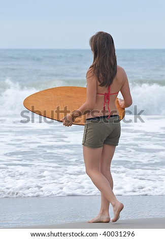 Athletic teen girl prepares for a wave to bring her the surf that she needs to skim on the water surface.  Room for text at the top of the image.
