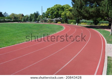 Athletic Track Curving Around Green Grass Field