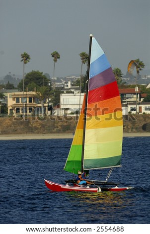 Athletic woman adjusts rigging on her yacht in Mission Bay, San Diego, California with a parasail in the background.