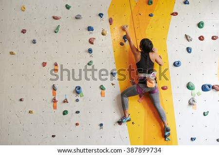 Athletic woman climbing indoors, view from the back #387899734
