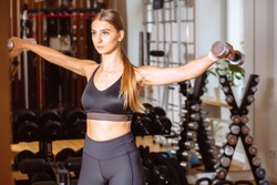 Athletic woman doing exercise for arms. Photo of muscular fitness model working out with dumbbells. Strength and motivation Healthy lifestyle, sport, beauty, training, goal concept.