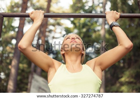 Athletic woman doing pull up