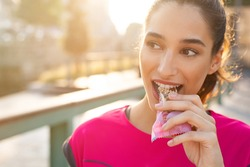 Athletic woman eating a protein bar. Closeup face of young sporty woman resting while biting a nutritive bar. Fitness beautiful woman eating a energy snack outdoor.