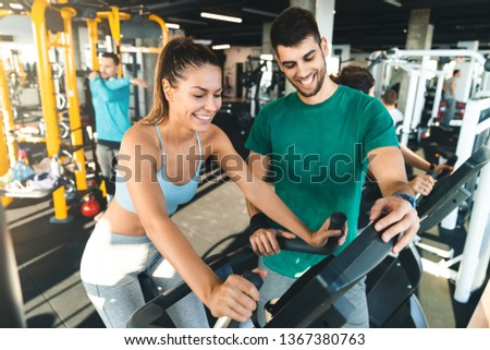 Athletic woman exercising with her coach during cross training in a gym