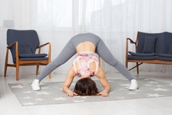 athletic woman in gray leggings with her legs wide apart bends upside down in a home interior, stretching exercises.