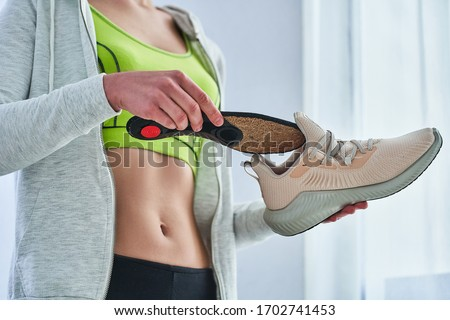 Athletic woman in sportswear with soft orthopedic insoles and sneakers for jogging. Treatment, prevention of flat feet and foot diseases, arch support. Foot comfort. Wearing sports comfortable shoes