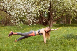 Athletic woman is planking outdoors in the blooming park in spring. Sporty girl is dressed in grey sport suit.