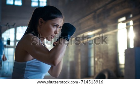 Athletic Woman is ready for Punch Punching Bag. She's Strong and Gorgeous Woman. They Workout in a Gym. #714513916