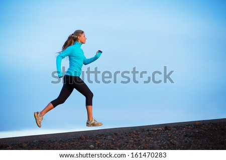 Athletic woman jogging outside training outdoors Running on road at sunset