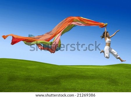 Athletic woman jumping on a green meadow - stock photo