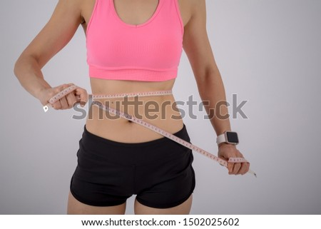 Athletic woman measuring her waist by measure tape over white background