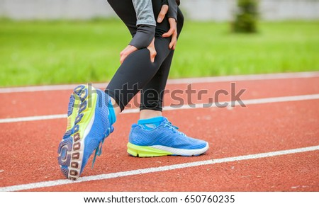Athletic woman on running track has calf cramp and touching hurt leg during workout