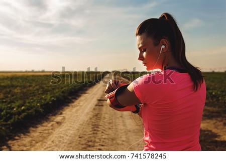 Athletic woman preparing run on dirt road.