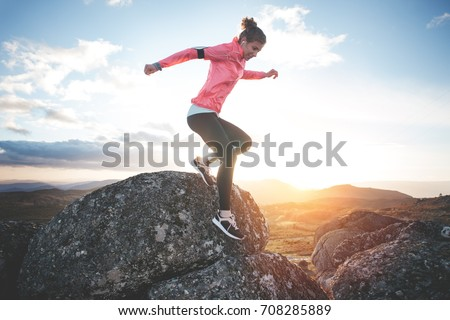 Athletic woman running in the mountains at sunset against the backdrop of a beautiful landscape. Sport tight clothes. Intentional motion blur. #708285889