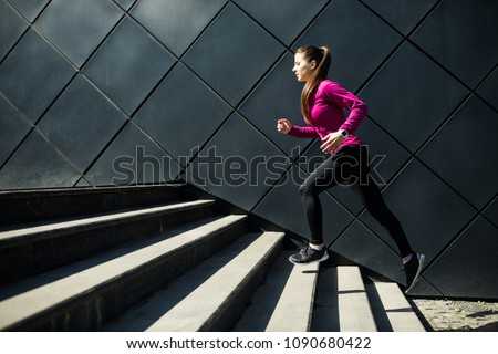 Athletic woman running up stairs during cardio #1090680422