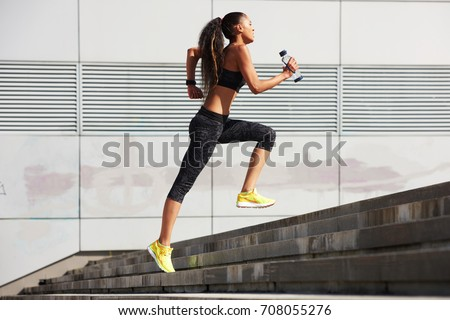 Athletic woman running up to the stone stairs with bottle of water in City  with fitness tracker