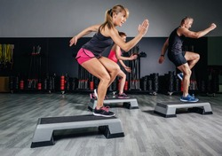 Athletic woman trainer doing aerobic class with steppers to people group on a fitness center. Sport and health concept.