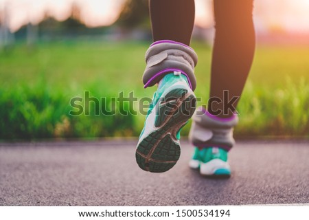 Athletic woman walks with sports weights to strengthen muscles and endurance during workout outdoor. Healthy and sports lifestyle. Be fit