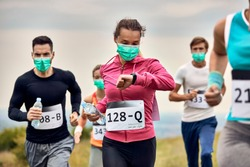 Athletic woman wearing face mask and looking at her wristwatch while running marathon in nature.