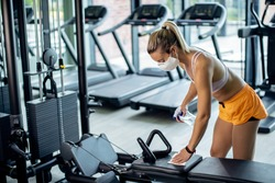 Athletic woman with face mask cleaning exercise machine with disinfectant while exercising in a gym during coronavirus epidemic.